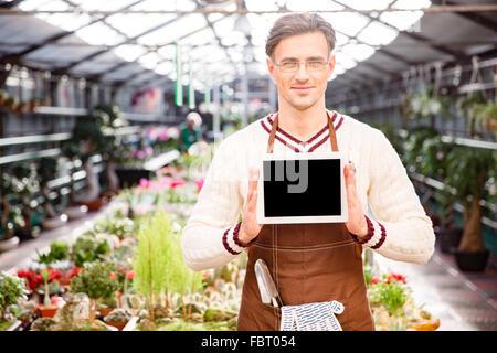 Bel homme debout jardinier et montrant des émissions de tablette écran vide Banque D'Images