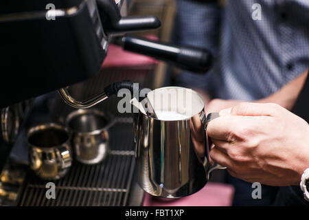 Waiter pouring milk Banque D'Images