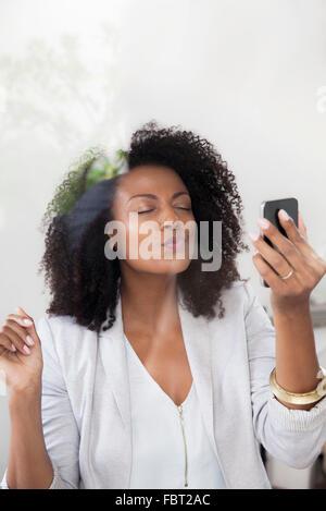 Woman blowing kiss at smartphone tout en faisant du chat vidéo Banque D'Images