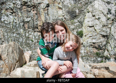 La mère et l'enfant assis sur rock formation, portrait Banque D'Images