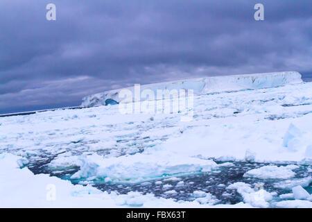 Iceberg tabulaire dans champ de glace flottante en Antarctique paysage coucher du soleil. Banque D'Images