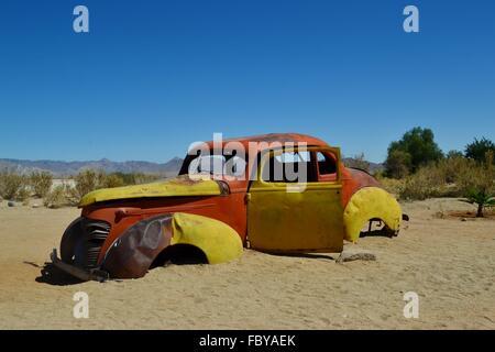 Abandonnée, la rouille et ventilées vieille voiture dans un désert Banque D'Images