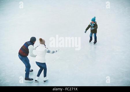 Petit garçon debout sur des patins sur la patinoire et à la recherche à ses parents Banque D'Images