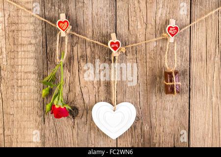 Rose rouge avec blanc forme coeur et chocolat sur fond de bois. Concept d'amour. Banque D'Images