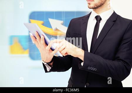 Image composite de mid section of a businessman using digital tablet pc Banque D'Images