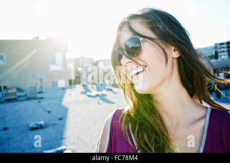 Mixed Race woman smiling on urban rooftop