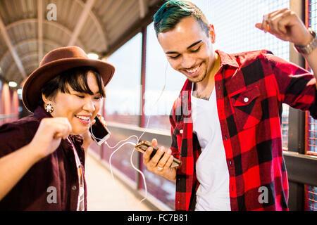 Le partage de deux écouteurs pour écouter de la musique Banque D'Images