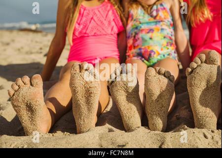 Sœurs de race blanche avec pieds de sable sur la plage Banque D'Images