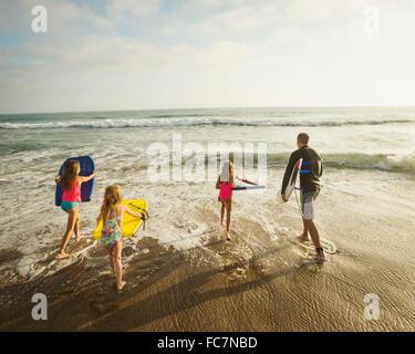 Portrait père et filles jouant dans les vagues sur la plage Banque D'Images