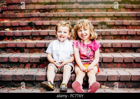 Des enfants de race blanche sitting on steps Banque D'Images