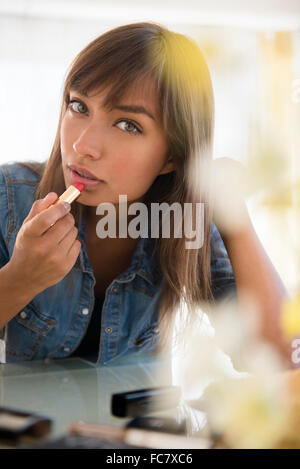 Mixed Race woman applying lipstick Banque D'Images