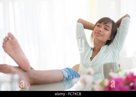 Barefoot mixed race woman relaxing