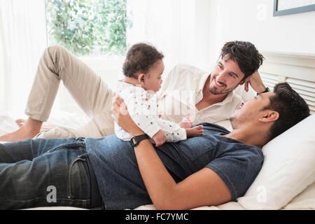 Les pères gays jouant avec son bébé sur le lit Banque D'Images