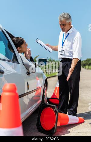 L'apprenti conducteur femelle s'excuser auprès d'instructeur en colère suite à l'utilisation de plus de traffic Banque D'Images