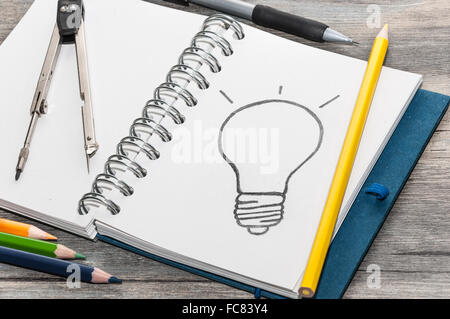 Livre avec un dessin d'une ampoule Banque D'Images