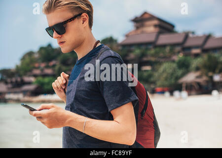 Caucasian man using cell phone on beach Banque D'Images