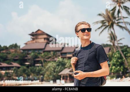 Caucasian man walking on beach Banque D'Images