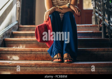 Caucasian woman sitting on stairs Banque D'Images
