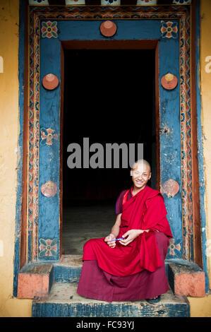 Jeune moine assis dans une porte, Punakha, Bhoutan, Asie Banque D'Images