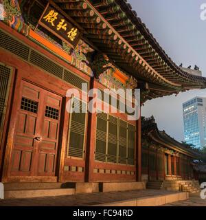 Palais Deoksugung, bâtiment traditionnel coréen, éclairé au crépuscule, avec un bâtiment moderne dans la distance, Banque D'Images