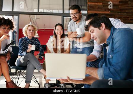 Équipe de créatifs à la collègue au plan de projet montrant sur son ordinateur portable. Groupe varié de jeunes ayant une réunion Banque D'Images