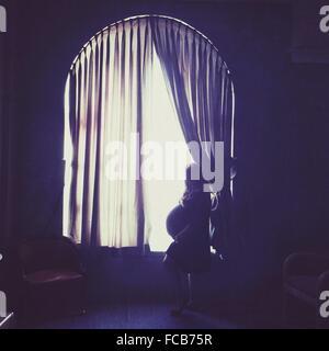 Vue de côté de femme enceinte looking out Window At Home Banque D'Images