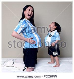Heureux fille imitant mère enceinte à la maison Banque D'Images