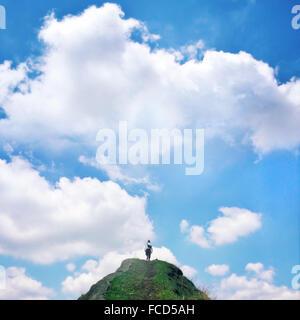 Low Angle View of Woman walking up rock contre le ciel bleu et nuages Banque D'Images