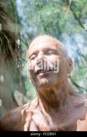 Close-up of smiling man prendre une douche à l'intérieur Banque D'Images