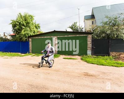 Businessman riding bicyclette d'enfant