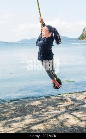 Une fille, 12, balançoires sur une corde sur l'île Saturna (Colombie-Britannique), Canada. Banque D'Images