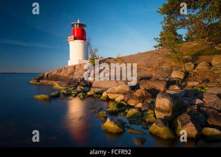 Le phare sur la côte rocheuse de l'île de l'archipel suédois Yxlan dans l'archipel, près de Stockholm, au coucher Banque D'Images