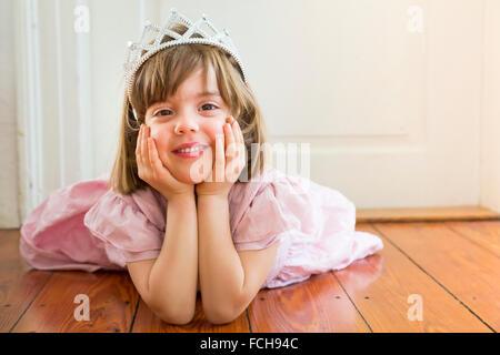 Portrait of smiling little girl habillé comme une princesse couchée sur plancher en bois Banque D'Images