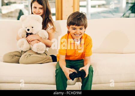 Boy playing video game in living room sister holding teddy bear Banque D'Images