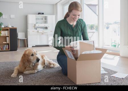 Souriante jeune femme à genoux sur le sol à côté de son chien de déballer une parcelle Banque D'Images