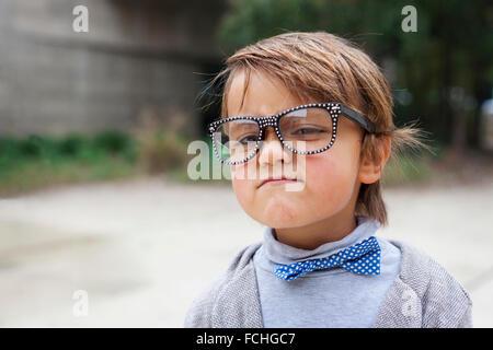 Portrait de jeune garçon portant des lunettes surdimensionnées et cravate garçon faire drôle de visage Banque D'Images