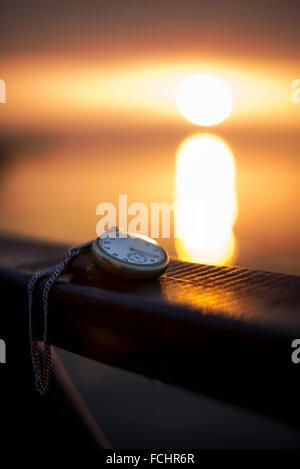 Montre de poche et la chaîne sur le coucher du soleil près du bord de l'eau. Banque D'Images