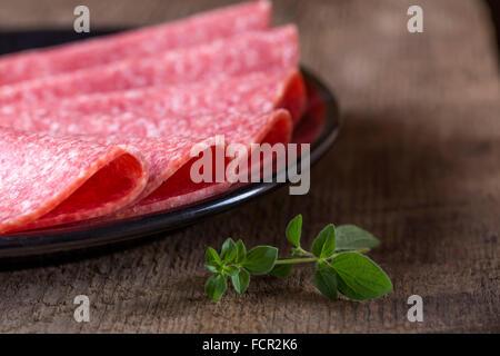 Tranches de salami sur la plaque noire sur fond rustique en bois Banque D'Images