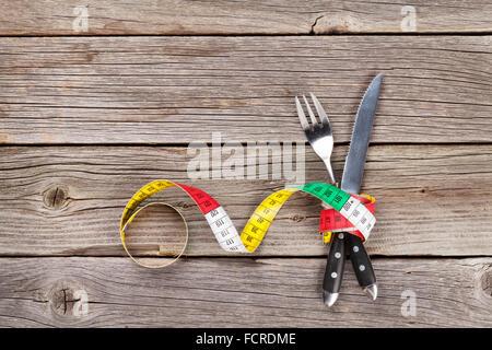 Concept d'aliments sains. La fourchette, le couteau et le ruban à mesurer sur la table en bois. Top View with copy Banque D'Images