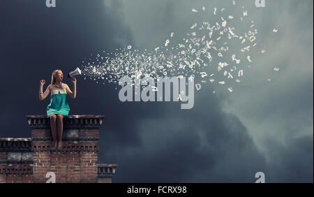 Jeune femme assise sur le toit et crier dans un mégaphone Banque D'Images