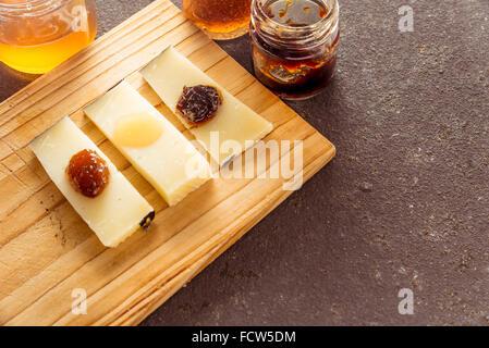 Une composition de tranches de fromage pecorino italien avec des confitures de différentes saveurs sur une planche Banque D'Images