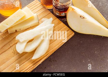 Une composition de tranches de fromage pecorino italien avec des confitures et les poires sur une planche à découper Banque D'Images
