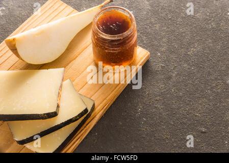 Une composition de tranches de fromage pecorino italien avec de la confiture et les poires sur une planche à découper Banque D'Images