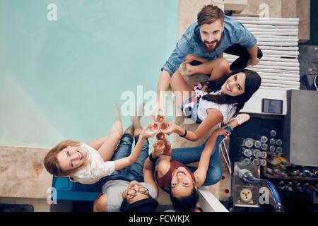 Vue de dessus de groupe d'amis toasting at party par une piscine et à la caméra jusqu'à sourire. Les jeunes multiraciale Banque D'Images