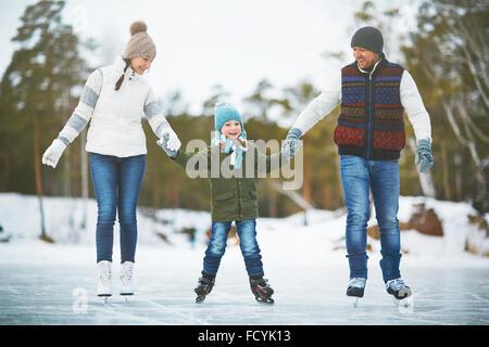Cute boy et ses parents patiner sur la patinoire Banque D'Images