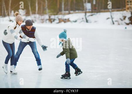 Les jeunes parents avec les bras tendus à la recherche à leur fils sur patinoire Banque D'Images