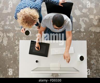 Vue supérieure de jeunes graphistes travaillant dans le bureau. À l'aide de tablette graphique, numérisées et stylo numérique ordinateur de bureau. L'homme s