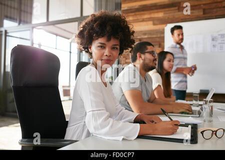 Portrait of businesswoman sitting at une présentation d'affaires avec des collègues dans la salle. Femme africaine avec un collègue