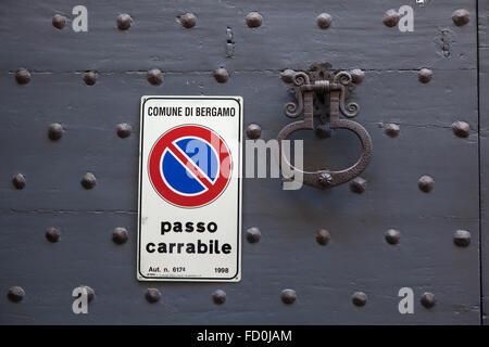 Vieux métal doorknocker et No Parking sign sur la porte en bois peint noir avec rivets fixes à Bergame, Lombardie, Italie.