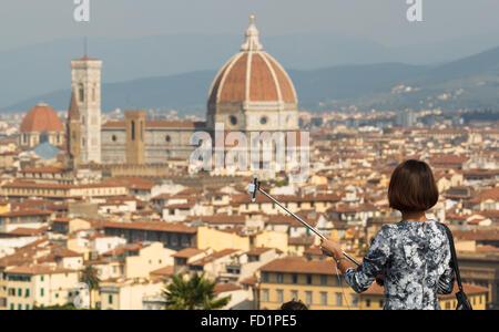 Une jeune femme se prépare à prendre un en selfies Piazzale Michelangelo, Florence, Toscane, Italie. Banque D'Images